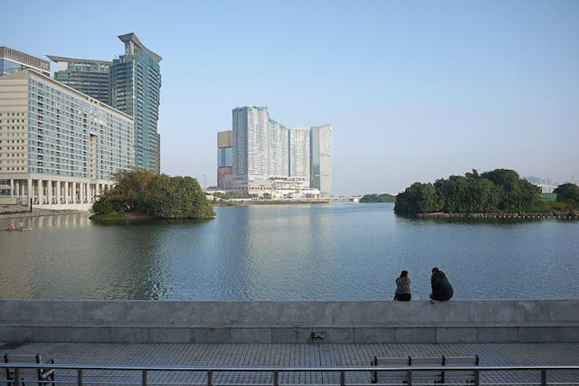 two people sitting at Nam Van Lake in Macau