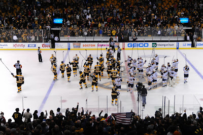 Bruins and Sabres players salute the Boston fans after the game