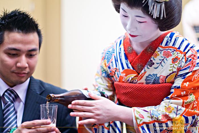 A Geisha Serving Asahi Beer at Sakura Jaya in Tokyo
