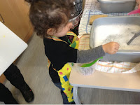 toddler wearing an apron washing up using a grey bowl on a table with tea towels underneath.