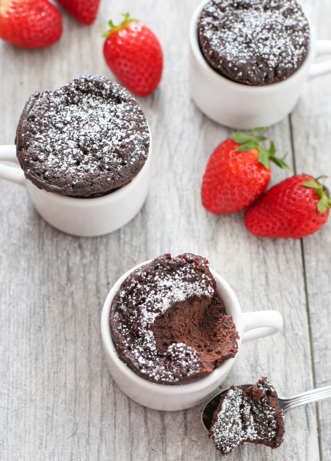 top-down photo of three chocolate mug cakes dusted with powdered sugar