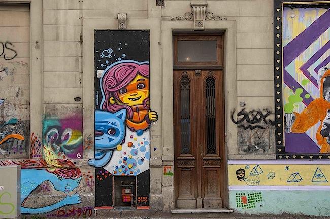 La fachada de un edificio donde se pueden ver dos puertas, una de ellas es un graffiti