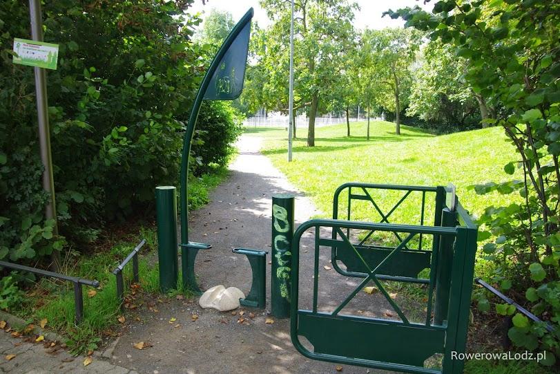 Wejście do parku - rower trzeba wprowadzać przez tę prowadnicę po lewej stronie, zaś elementy po prawej są ruchome dzięki czemu może zmieścić się tam nie tylko pieszy ale i cały wózek dziecięcy.