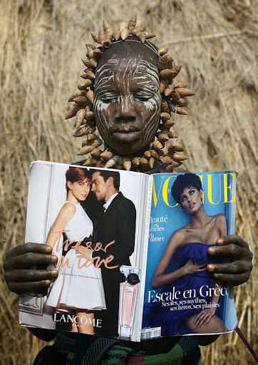 A Mursi tribe woman discovers Vogue magazine, Ethiopia.jpg