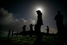 Un grupo de personas camina por la playa a la luz de la luna llena.