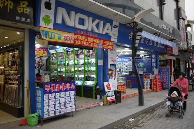 Store with large Nokia sign also showing signs for Apple, Android, and Samsung