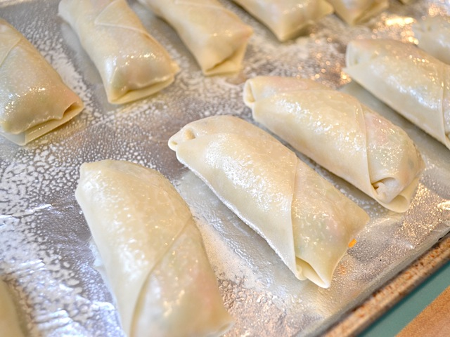 rolled egg rolls placed on baking sheet lined with tin foil ready to bake