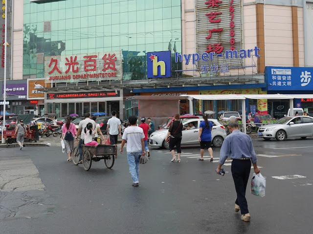 girl riding in the back of a tricycle cart crossing a street in Changde