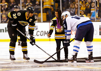 Gold medal gymnast Aly Raisman drops the puck in front of Zdeno Chara and Andrew Ladd