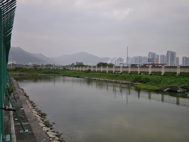 a strip of water with mountain and apartment complexes in the background