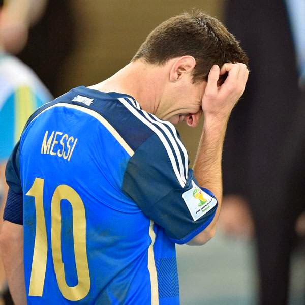 Argentina's Lionel Messi scratches his head as he goes up to get his runners-up medal after the World Cup final soccer match between Germany and Argentina at the Maracana Stadium in Rio de Janeiro, Brazil, Sunday, July 13, 2014.
