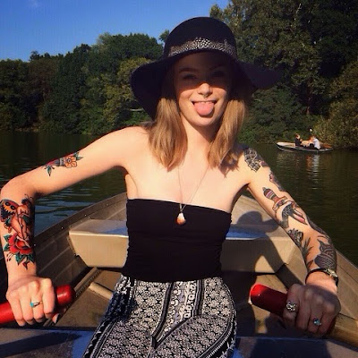 A picture of a tattooed woman wearing a floppy hat and rowing a boat in Central Park, New York