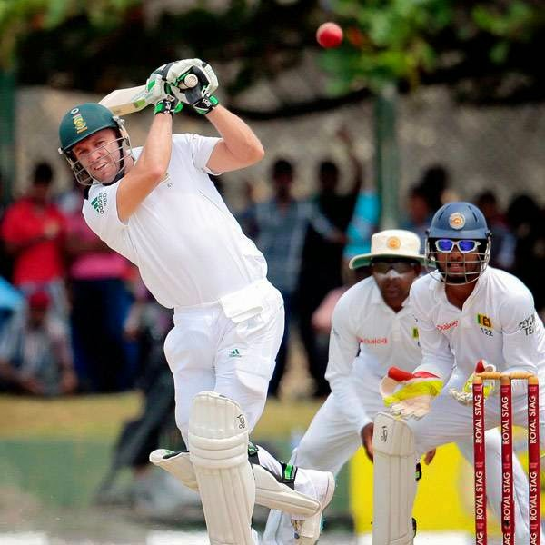 South African batsman AB de Villiers plays a shot as Sri Lankan wicketkeeper Dinesh Chandimal, right, and Mahela Jayawardene watch during the fourth day of the first test cricket mach between Sri Lanka and South Africa in Galle, Sri Lanka, Saturday, July 19, 2014.