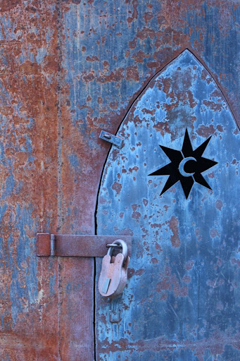 a pointy door in what looks like a rusty metal rocket