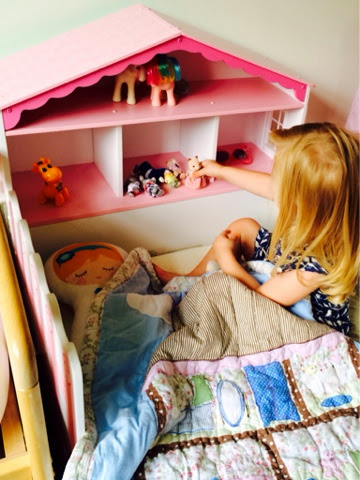 Maegan playing with Sylvanian families on her dollhouse bed