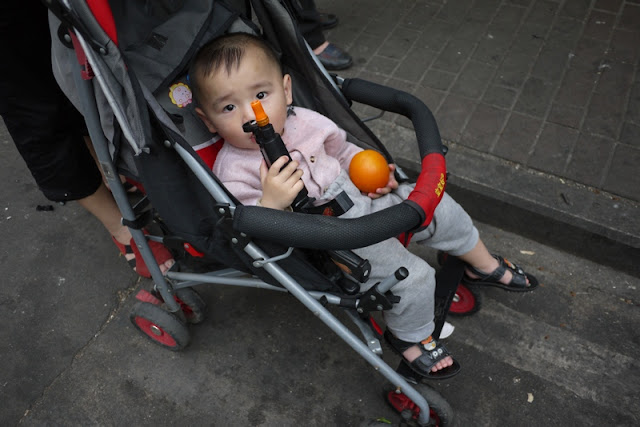 Young child in a stroller holding an orange and play gun in Zhuhai, China