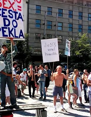 David, přítel Tomáše Adámka, pózuje s našimi skromnými transparenty vedle účastníka průvodu, kterému vzkazujeme: Vysvobození z homofóbie je možné!