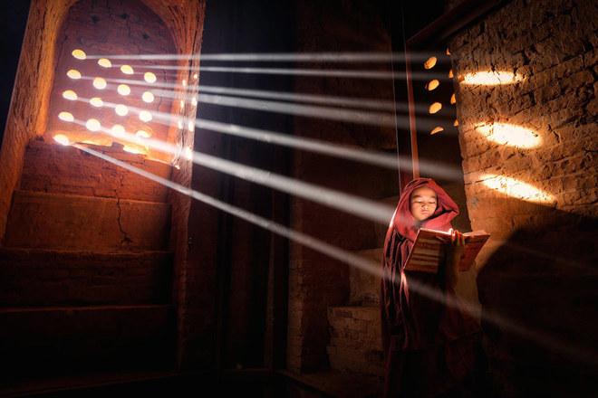 """Một chú tiểu chăm chú đọc sách trong một ngôi chùa ở thành phố cổ Bagan, Burma (Myanmar) - Tác phẩm """"LightSource"""" (Nguồn sáng)."""