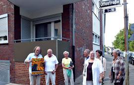 Kleine Gruppe vor Mehrfamilienhaus.