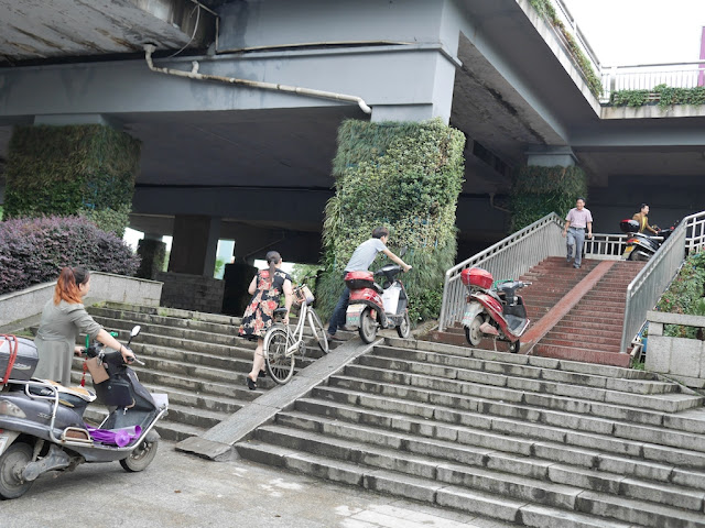 people pushing motorbikes up a steep stairway ramp