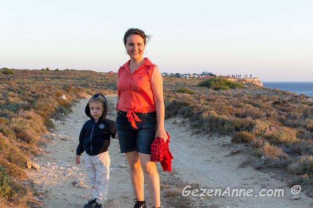 Bozcaada'da, Polente'ye doğru yürürken, arkada güneşin batışını bekleyenler