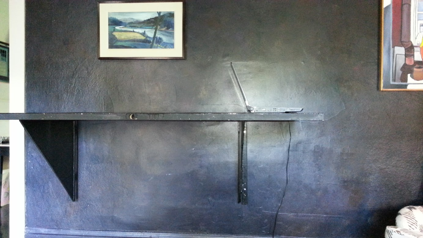 The wall table lifted up on wall-mounted supports, with a laptop computer sitting on it