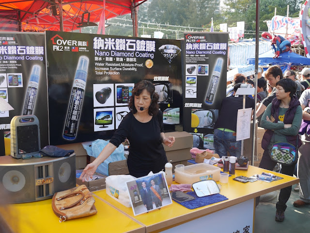 woman at a stall selling and demonstrating Nano Diamond Coating