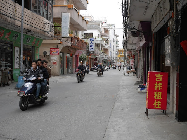 three young men riding a motorbike in Yangjiang, China