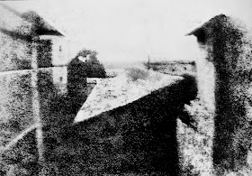 View from the Window at Le Gras, the first successful permanent photograph created by Nicéphore Niépce in 1825, Saint-Loup-de-Varennes. Captured on 20 × 25 cm oil-treated bitumen. Due to the 8-hour exposure, the buildings are illuminated by the sun from both right and left.