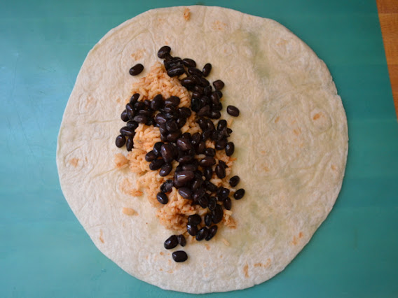tortilla laid flat on counter and filled with rice and black beans
