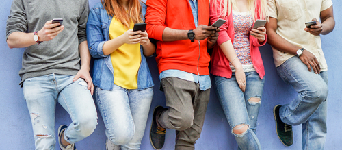 A line of young adults holding cell phones
