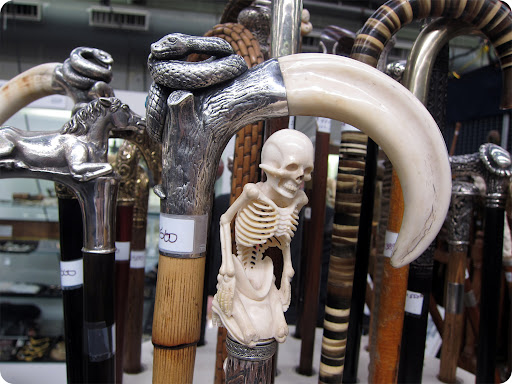These cane handles are a little more macabre—carved out of bone or ivory, here is an intricate skeleton and one with a snake resting on a curled tusk.