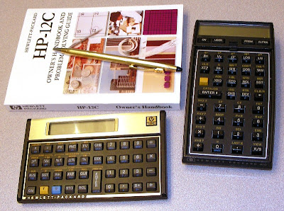 HP-12C calculator and manual next to HP-41 scientific handheld calculator