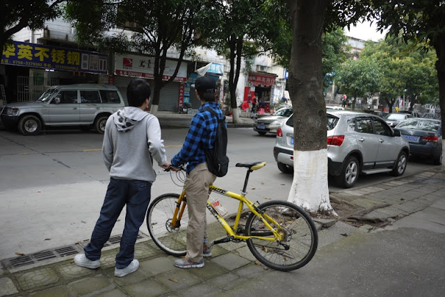two young men stranding next to a bicycle in Zhuhai, China