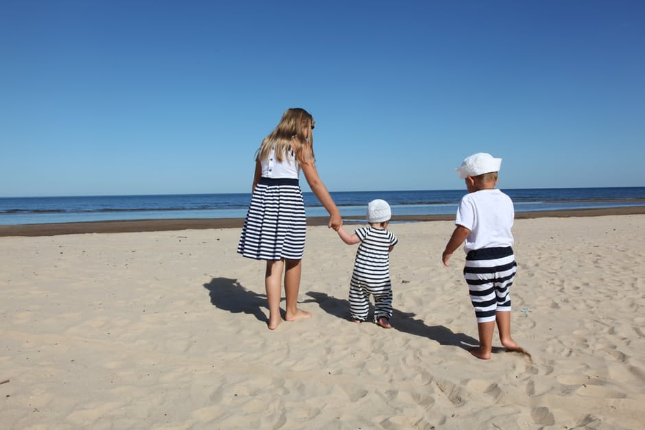 Young girl and two baby brothers playing on a beach