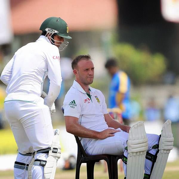 South Africa cricketer AB de Villiers (R) and teammate Quinton de Kock (L) take a water break during the fourth day of the opening Test match between Sri Lanka and South Africa at the Galle International Cricket Stadium in Galle on July 19, 2014.