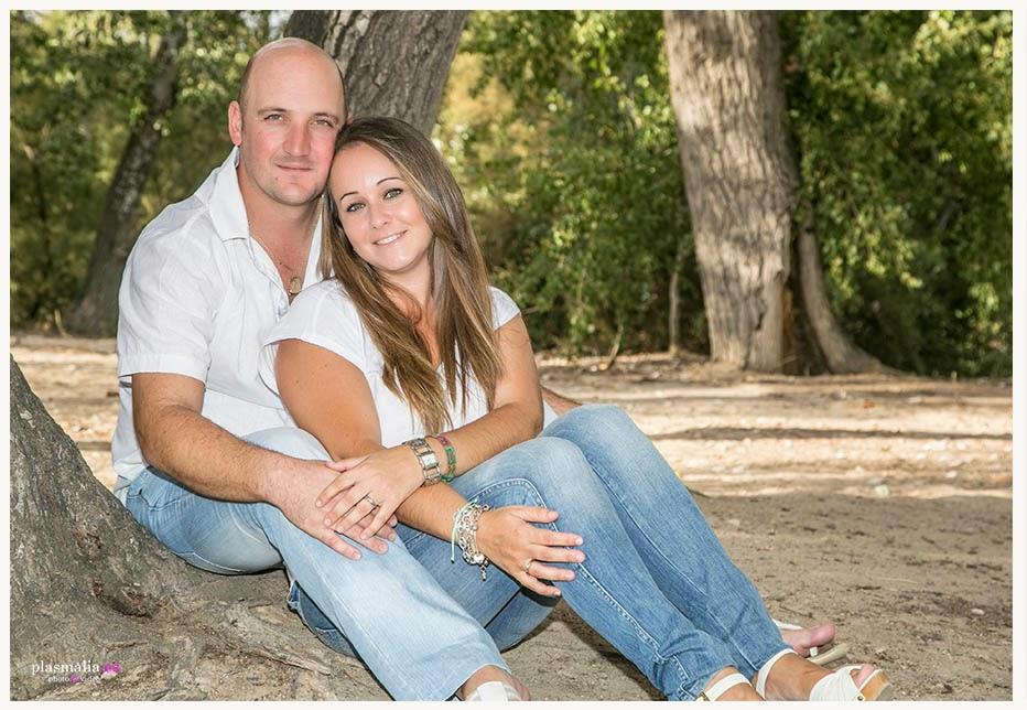 Retrato en familia. Mamá y papá abrazados y sentados junto a un árbol.