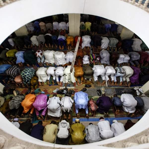 Muslims gather to attend Eid-al-Fitr prayers, in Treichville, in Abidjan.