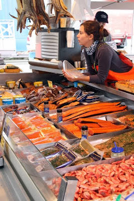 Woman selling salmon at the Bergen fish market in Norway