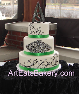 Three tier white fondant custom designed wedding cake with black scroll work, green ribbons and handcrafted topper