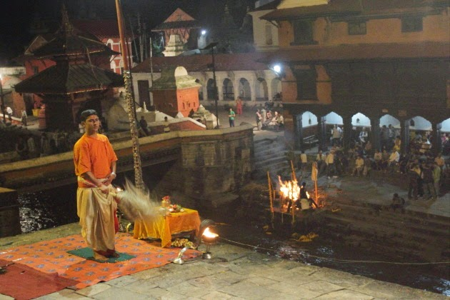 Maha Aarti and a cremation in the background at Pashupatinath Temple, Kathmandu