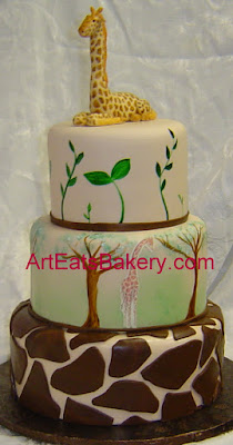 Three tier jungle theme baby shower custom cake with hand painted trees, leaves and fondant giraffe topper
