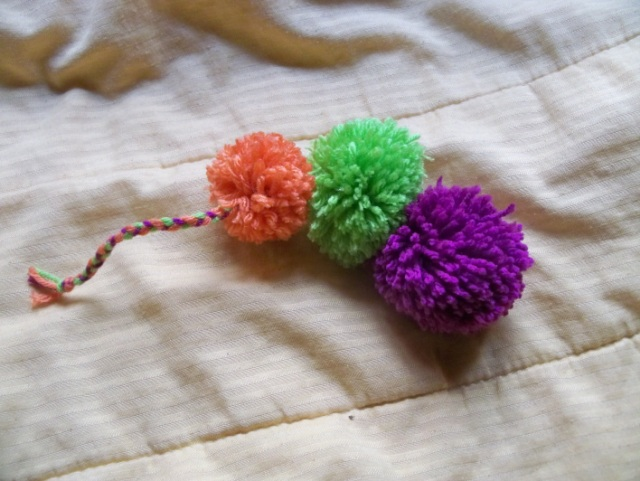 Three pom-poms with a braided tail
