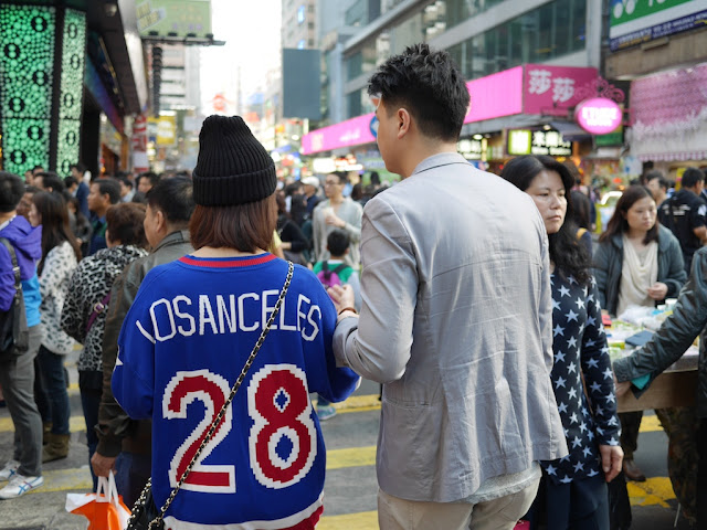 "man walking with a woman wearing a ""Los Anceles 28"" sport team jersey at Sai Yeung Choi Street South"