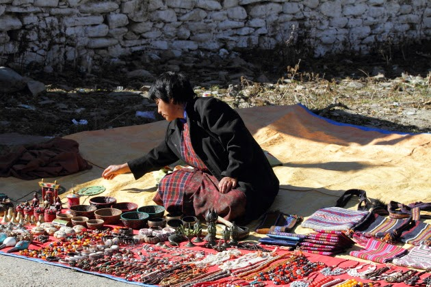 Street hawker selling her wares in front of Jampey Lakhang, Bumthang