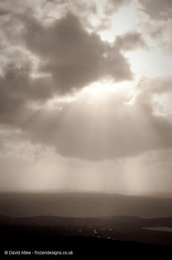 Sun rays breaking through cloud across the coastline