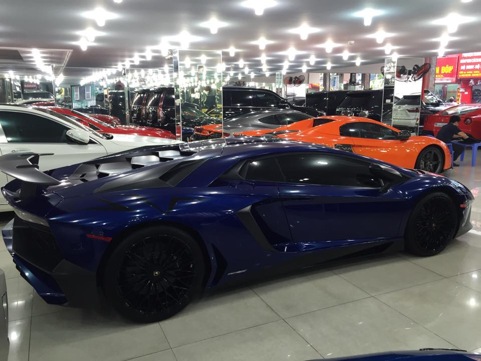 Lamborghini Aventador SV xanh độc đứng cạnh rất nhiều siêu xe khác trong showroom