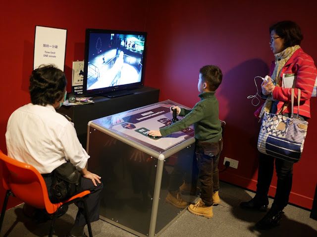 boy at the Tyrannosaurus Command Centre playing with controls and looking at live video of the area around the Tyrannosaurus
