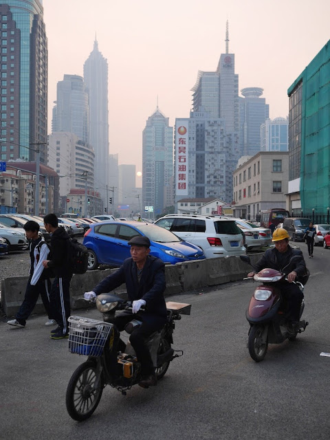 two men on motorbikes and two boys walking on Pudong Avenue in Shanghai