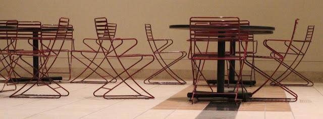 red wire chairs in the lobby of an office building
